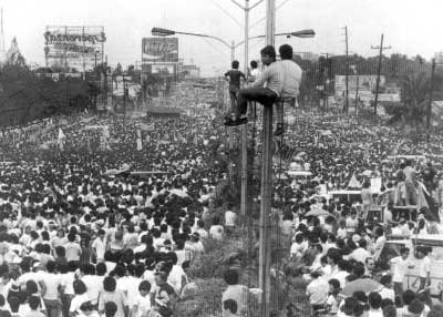 An iconic photo of the EDSA Revolution in the Philippines in February 1986 showing hundreds of thousands of people filling up Epifanio delos Santos Avenue (EDSA). The view is looking northbound towards the Boni Serrano Avenue-EDSA intersection. (Photo by Joey de Vera, taken from Wikimedia)