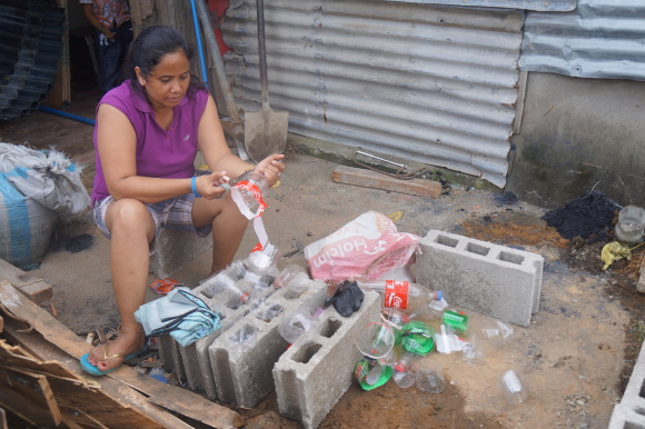 A housewife cuts up used plastic soda bottles for use in a 'build back better' sewage system for her new, rising home at Barangay 62 in Tacloban City. Photo taken Nov. 4, 2014.