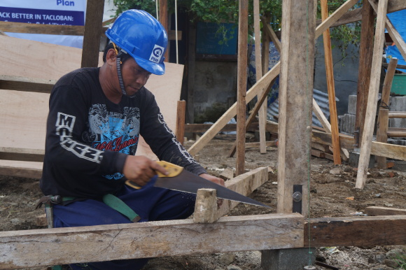 """""""Cash for work"""" in action: A carpenter works at a Plan International Philippines worksite in Barangay 62, Tacloban City. Photo taken on Nov. 4, 2014."""