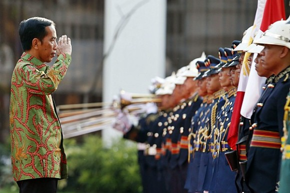 Indonesian President Joko Widodo salutes the colors during a welcoming ceremony for Widodo at the Malacanang presidential palace in Manila February 9, 2015. Widodo will discuss with President Benigno Aquino matters of mutual concern, including migrant workers issues, maritime cooperation, defense, trade and investment, a foreign affairs press statement said.      REUTERS/Erik De Castro  (PHILIPPINES - Tags: POLITICS)